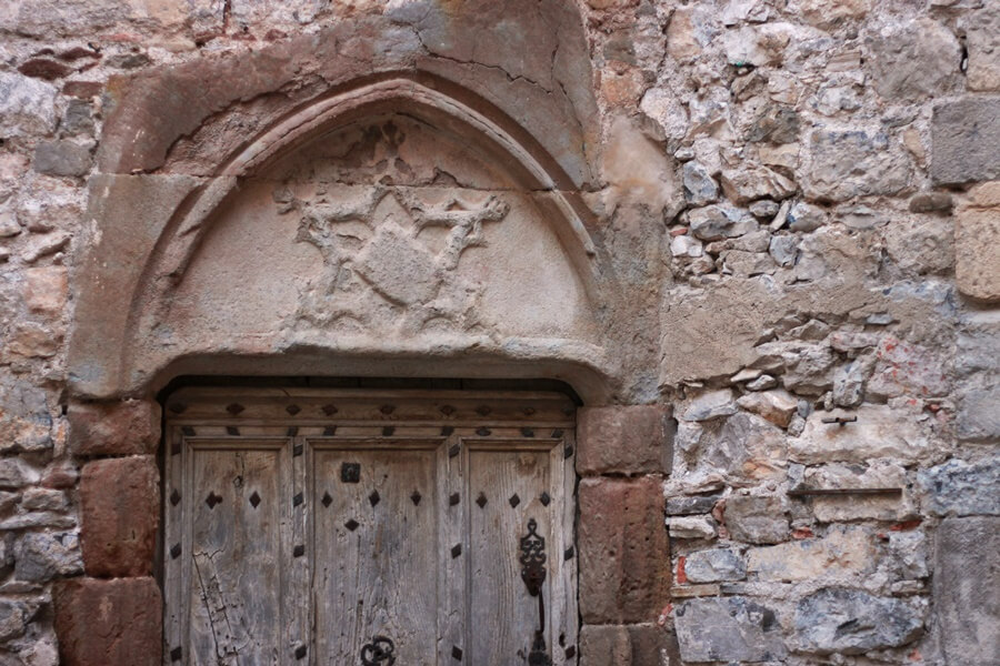 Exploring Lagrasse with Kids - carved stone and old wooden door